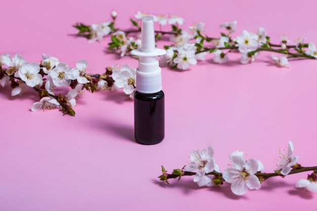 Аэрозоль для носа. аэрозольный баллончик на розовом фоне. макет. цветущая веточка. аллергия