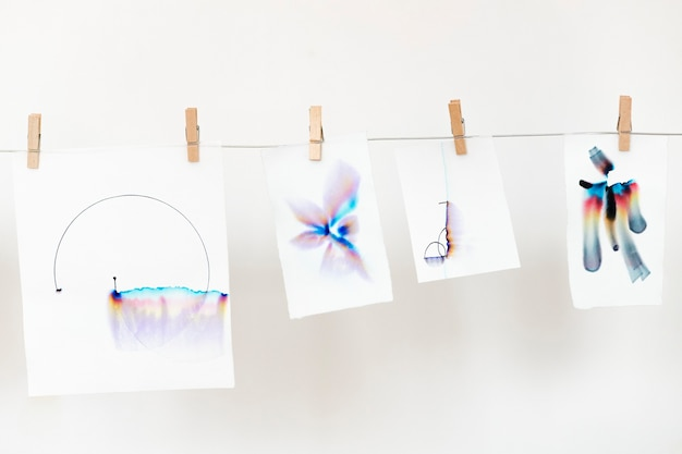 Aesthetic chromatography art on white papers hanging on a rope