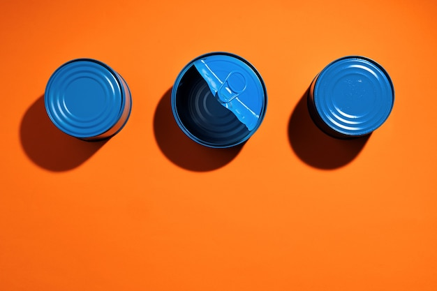 Aesthetic concept with blue painted tin can on orange surface