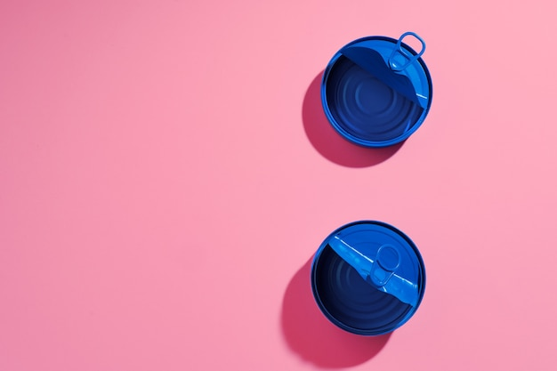 Aesthetic concept with blue painted tin can on pink surface