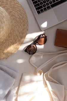 女性のファッションアクセサリーを使った審美的なクリエイティブな構成。スタイリッシュな女性のサングラス、麦わら帽子、買い物袋、白のラップトップ