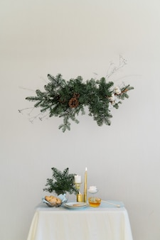 Aesthetic design for christmas with pine nobilis hanging garland, candles and table decorations .