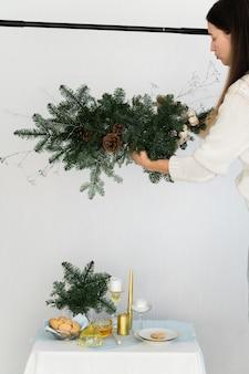 Эстетичный дизайн на рождество с подвесной гирляндой из сосны nobilis, свечами и украшениями для стола.