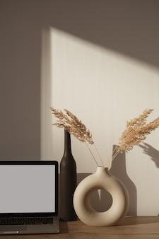 壁に日光の影がある審美的なホームオフィスデスクワークスペース。空白の画面のラップトップコンピューター