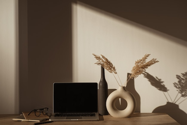 Aesthetic home office desk workspace with sunlight shadows on the wall.