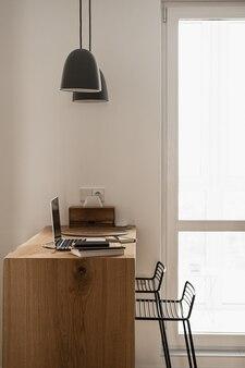 審美的な最小限の家、リビングルームのインテリアデザイン。ハンギングランプ、ラップトップコンピューター付き木製スタンド
