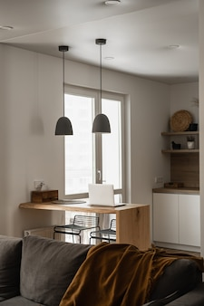 審美的な最小限の家、リビングルームのインテリアデザイン。チェック柄のソファ、ハンギングランプ、ラップトップコンピューター付きの木製スタンド