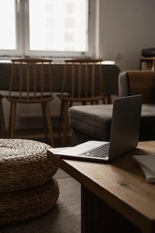 審美的な最小限の家、リビングルームのインテリアデザイン。ラップトップコンピューター、籐のプーフ、スツールと木製のテーブル