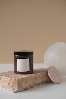 미적 미니멀 뷰티 케어 치료 개념. 중립 베이지에 대한 대리석 돌에 빈 바디 케어 크림 용기