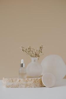 미적 미니멀 뷰티 케어 치료 개념. 중성 베이지에 대한 꽃과 돌에 유기 세럼 오일 화장품 병
