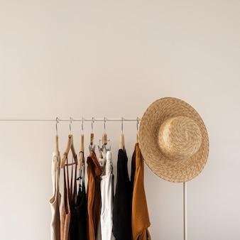 미적 미니멀 패션 인플 루 언서 블로그 개념. 여름 여성 드레스, 탑, 티셔츠, 흰 벽에 의류 선반에 밀짚 모자