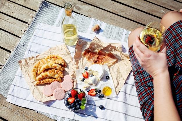 Эстетичный пикник на свежем воздухе с бокалами для вина, круассаном, сыром камамбер и фруктами.