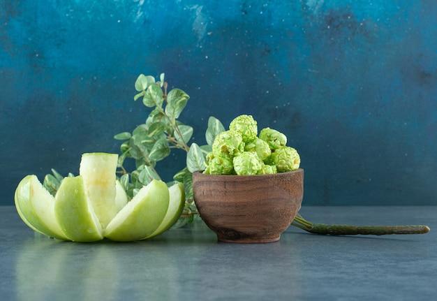 Posizionamento estetico di mela affettata in modo decorativo, ciotola di caramelle popcorn e un ramo decorativo su sfondo blu. foto di alta qualità