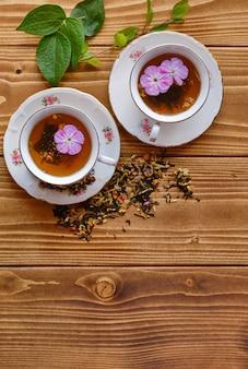 나무 탁자에 꽃이 든 차 한 잔의 미학적 샷