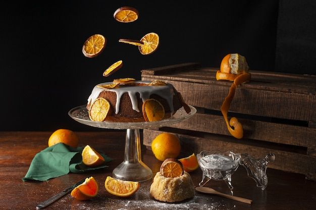 Эстетичный яркий снимок дольок апельсина, падающих на торт, покрытый сладкой сахарной глазурью