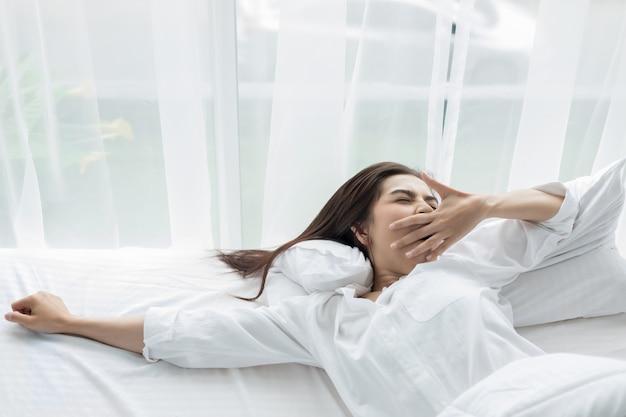 Азиатская женщина красивая молодая женщина улыбается, сидя на кровати и растяжения утром в спальне af