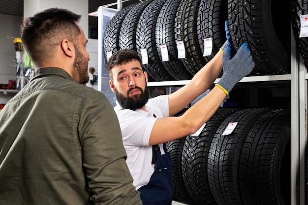 制服を着た気さくな自動車整備士がお客様の選択を助け、白人の若い男性が自動車用の新しいタイヤを購入するようになりました。稼働中