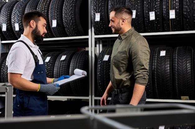 제복을 입은 상냥한 자동차 정비사가 선택으로 고객을 돕고 백인 젊은 남성이 자동차 용 새 타이어를 사러 왔습니다. 서비스 중