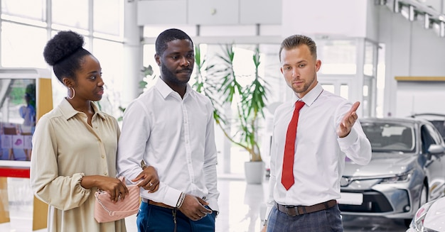 Affable caucasian car dealer consult customers