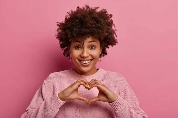 Affection and relationship concept. glad ethnic delighted woman shapes heart with hands, smiles positively, demonstrates love symbol, wears pink pastel sweater, gestures indoor. monochrome shot