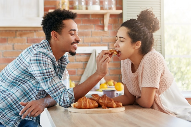 Affectionate bearded mixed race man feeds his girlfriend with tasty croissant which he baked by himself.