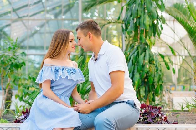 리조트에서 여행을 즐기는 큰 녹색 식물 위에 벤치에 앉아 다정한 커플