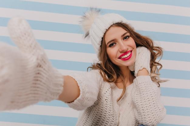 愛情深く、夢のような、巻き毛の茶色の髪のロマンチックな表情で、自分撮りのポーズをとっています。かわいい、暖かいニット帽とセーターの女性の屋内の肖像画