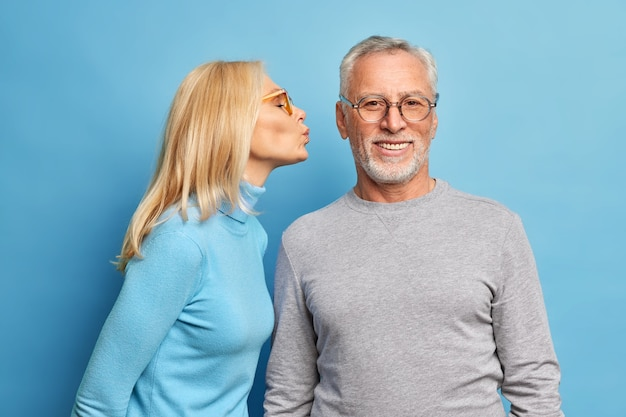 Affectionate elderly blonde woman going to kiss bearded husband in cheek expresses love