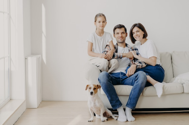 Affectionate family pose together on couch in empty spacious room with white walls, their favourite dog sits on floor