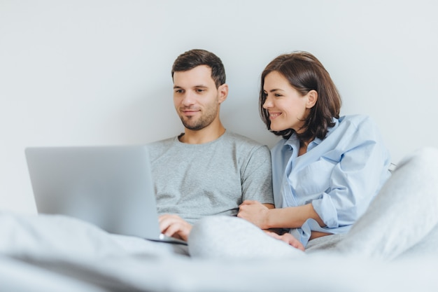 Affectionate female and male have joy together, watch film in bedroom on laptop computer.
