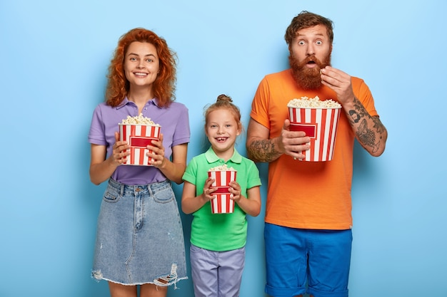 Affectionate ginger family posing with popcorn