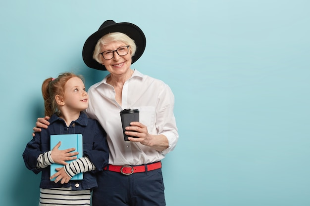 Affectionate grey haired grandmother in hat embraces small female child, loves her granddaughter, drinks takeaway coffee. curious little kid with pocketbook, listens advice from wise old woman.