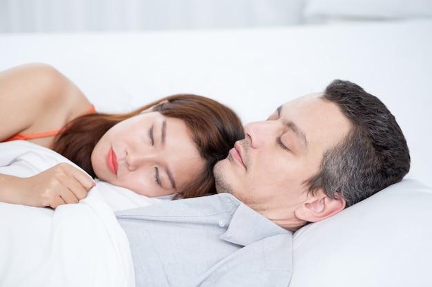 ベッドで眠っている愛情のある異人種カップル