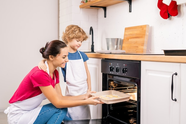 Affectionate little boy standing by his happy mother putting tray with biscuits into oven while cooking together