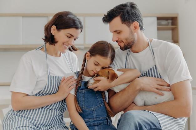 Ласковая маленькая девочка обнимает родословную собаку с любовью, мамой и папой. счастливая семья и их питомец