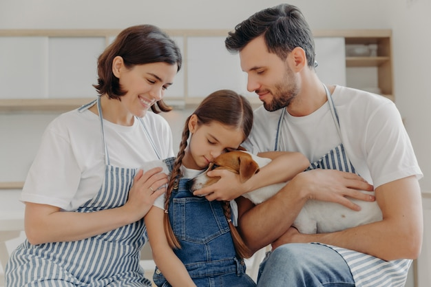 Affectionate little girl embraces pedigree dog with love, mother and father. happy family and their pet