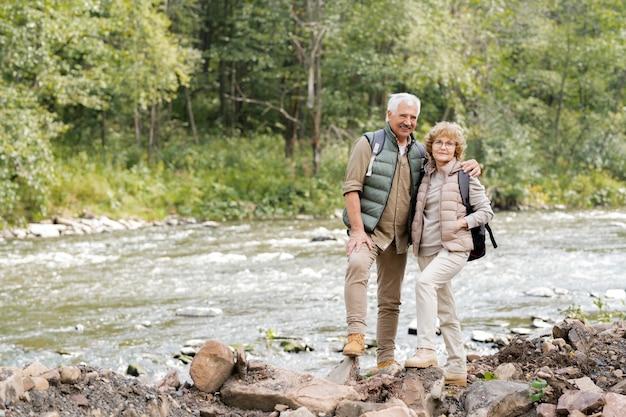 Ласковые зрелые супруги с рюкзаками стоят на камнях на берегу реки во время поездки в летние выходные