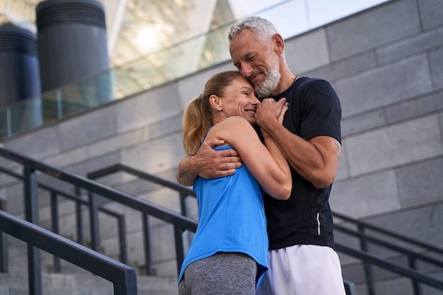 Ласковая пара средних лет, мужчина и женщина в спортивной одежде, обнимая друг друга стоя