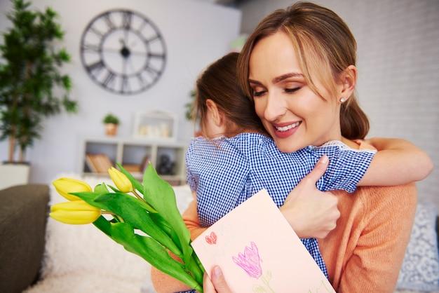 愛情深いお母さんと娘が家で抱きしめる