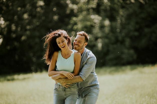 Ласковая молодая пара веселится на зеленой траве в парке