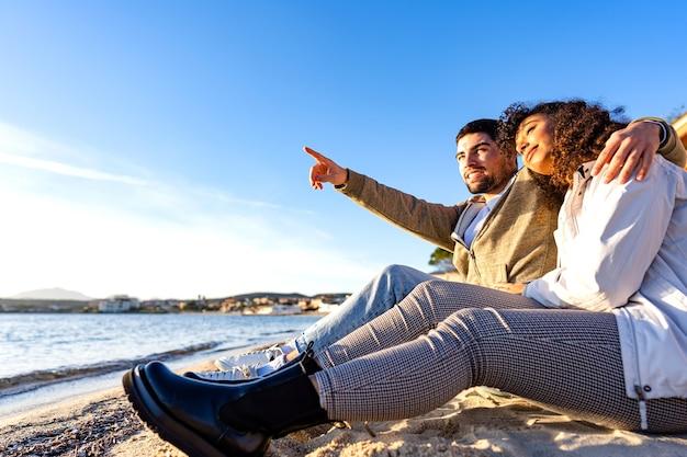 夕日を眺めながら隣同士の海の近くの海岸に座っている愛情のこもった若いカップル。冬の休暇旅行で地平線を指しているガールフレンドを抱きしめるハンサムな男