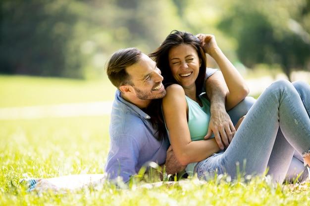 Ласковая молодая пара, сидящая на зеленой траве в парке