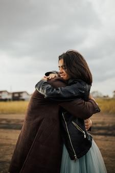 다정한 젊은 부부는 서로의 팔에 가까이 서서 웃고 사랑을 느끼고 있습니다.
