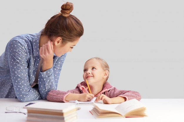 Affectionate young mother helps her little daughter with doing home assignment, pose at white desk with notebook and textbooks, look positively at each other, learn alphabet together, isolated