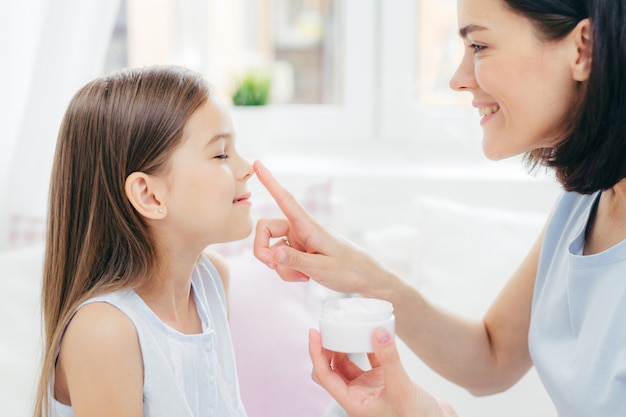 Affectionate young mum touches daughter`s nose, holds bottle of cream, enjoy togetherness, take care of skin