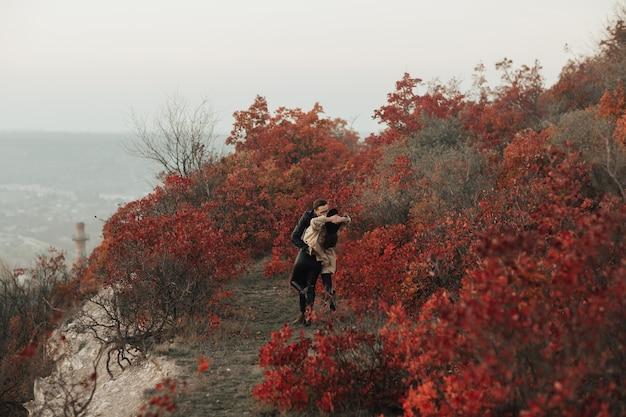 Ласковая молодая стильная пара обнимается и целуется в осеннем парке