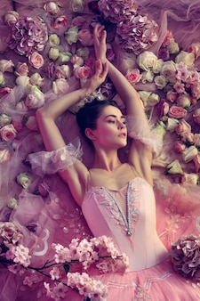 Affectivity. top view of beautiful young woman in pink ballet tutu surrounded by flowers. spring mood and tenderness in coral light. concept of spring, blossom and nature's awakening.