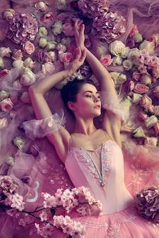 감성. 꽃으로 둘러싸인 핑크 발레 투투에서 아름 다운 젊은 여자의 최고 볼 수 있습니다. 산호 빛의 봄 분위기와 부드러움. 봄, 꽃, 자연의 각성 개념.