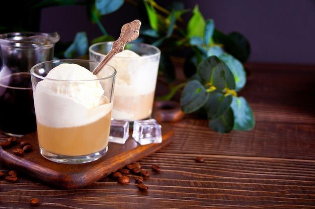 Кофе affogato с мороженым в очках на деревянном столе.