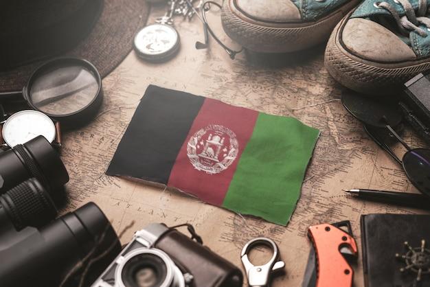 Флаг афганистана между аксессуарами путешественника на старой винтажной карте. концепция туристического направления.